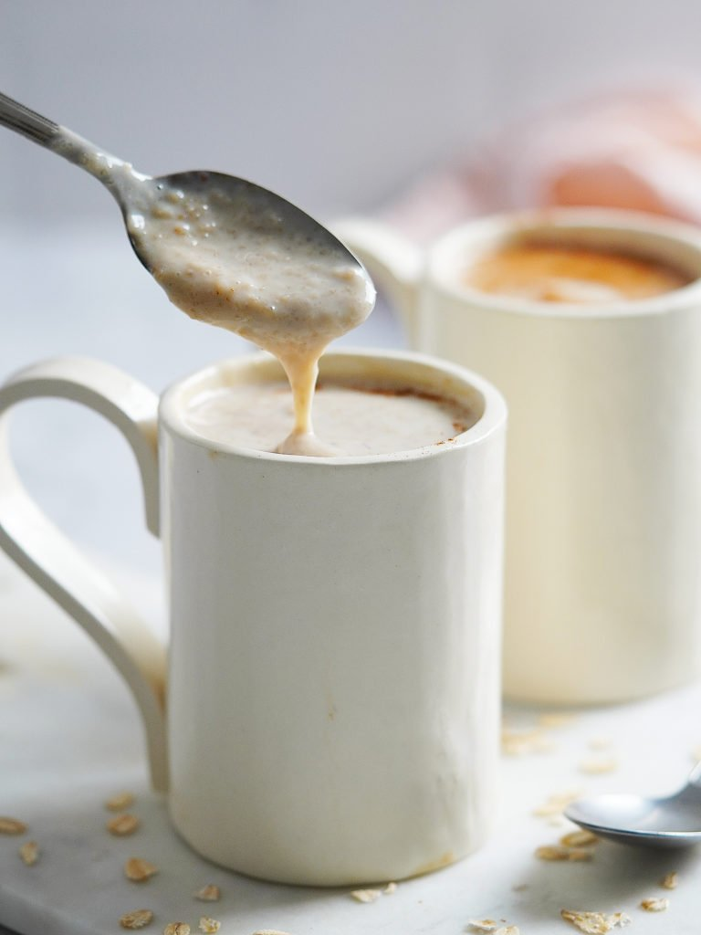 A white mug with a spoon dripping some oatmeal drink