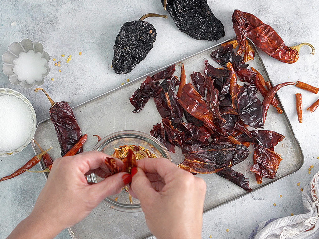 Two hands removing seeds from dried chiles