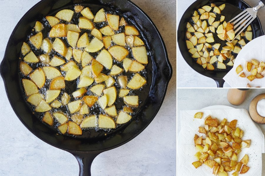 A skillet cooking sliced potatoes in oil