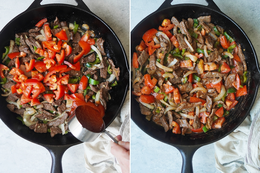 A skillet with cooked beef, onions, chiles & tomatoes