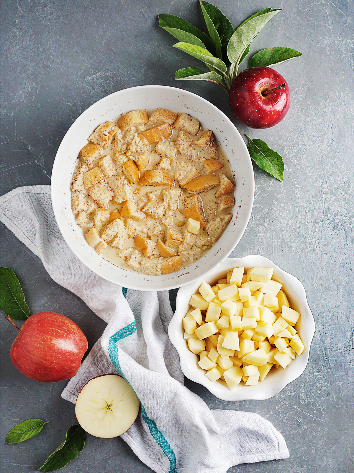 A bowl with bread soaking in egg & milk mixture and another bowl with apple chunks