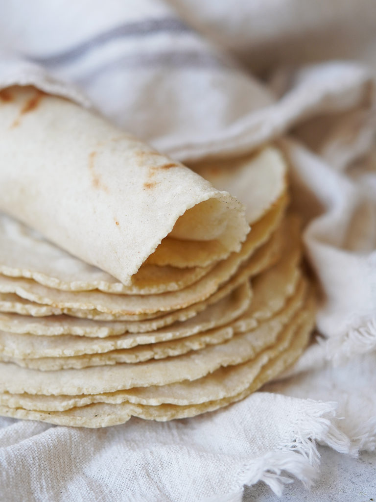 A stack of corn tortillas placed in a kitchen towel