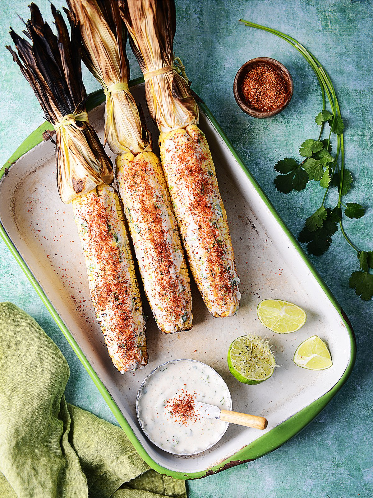 Three Elotes Asados on the cob on a white vintage tray on a green background