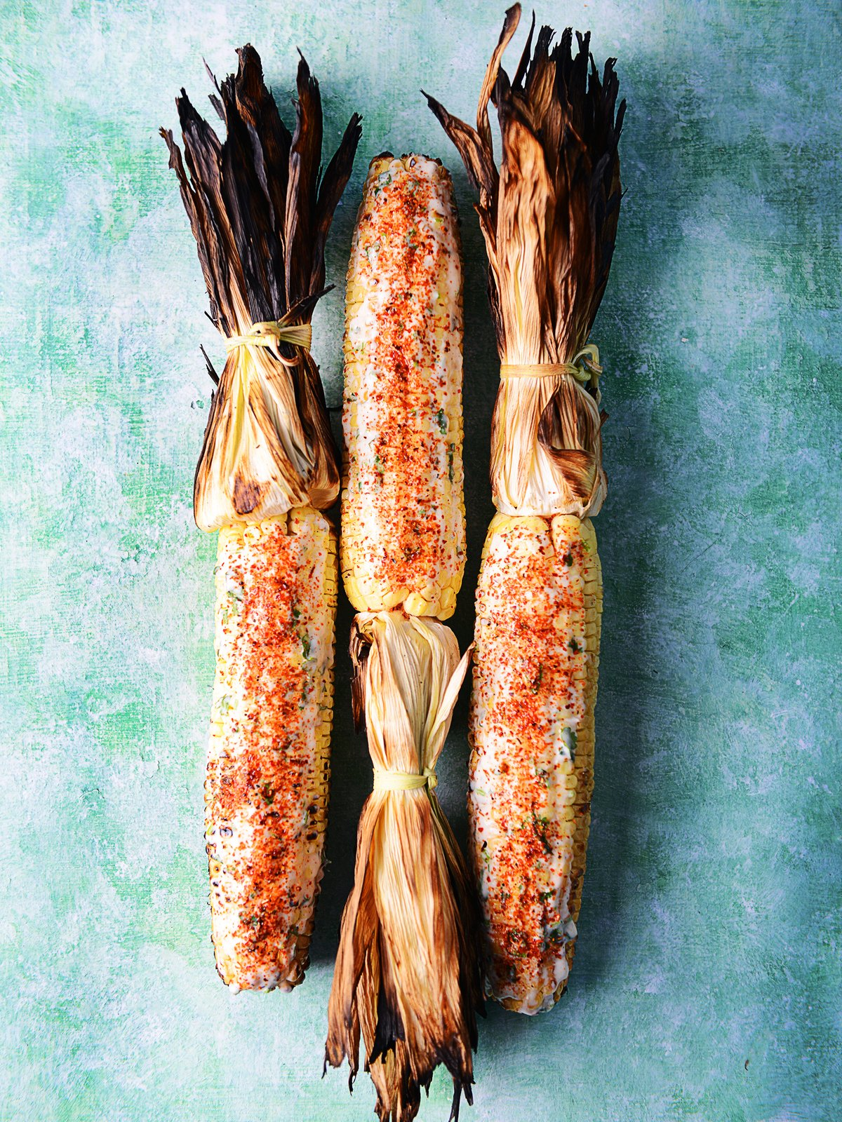 Three grilled corns on the cob placed on a green background