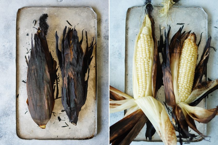 Two grilled corn on a small metal baking tray.