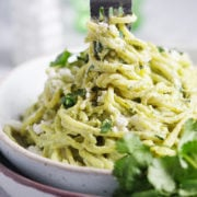 A white bowl with spaghetti being swirled with a fork. Cilantro on the side.