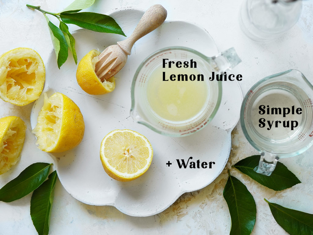 A white serving plate with fresh squeezed lemons, a cup with lemon juice and a cup with simple syrup