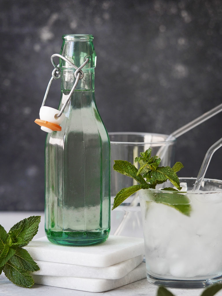 A green bottle with clear simply syrup. with mint as garnish