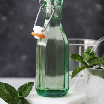 A green bottle with clear with mint as garnish
