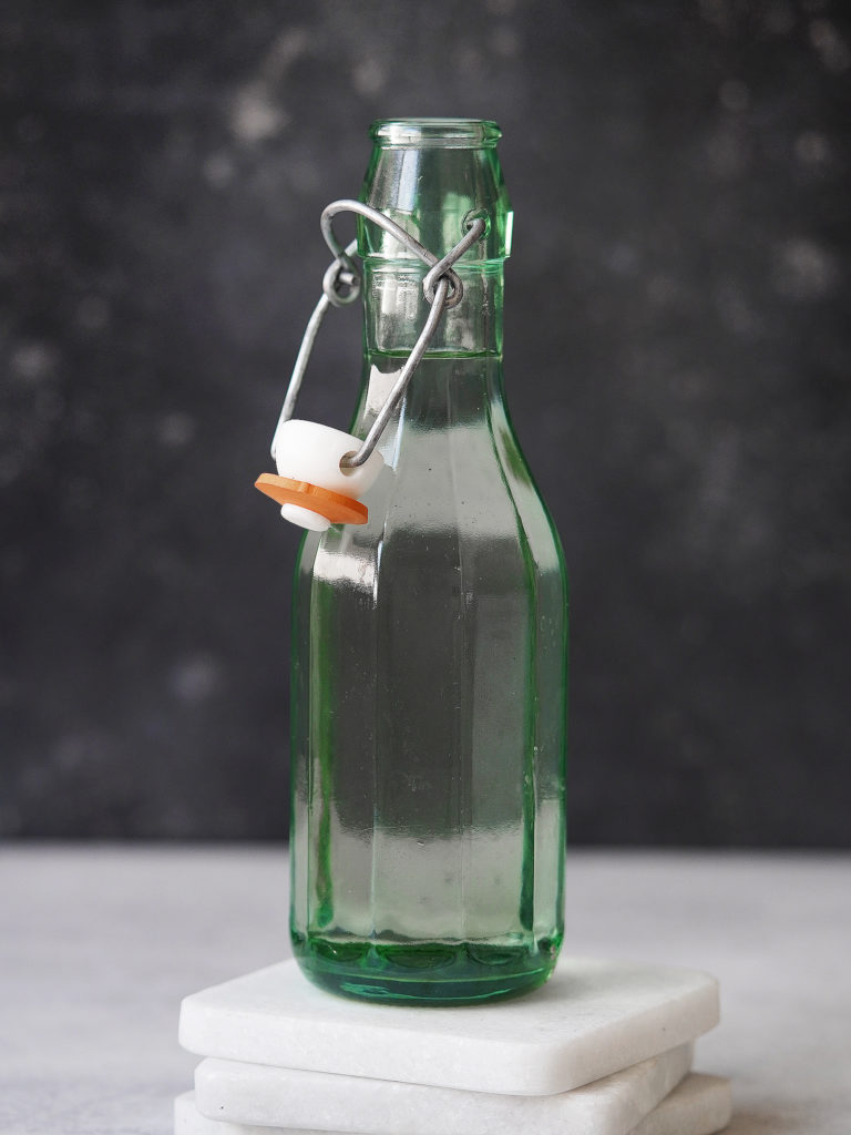 A green glass bottle with clear simply syrup. Dark background