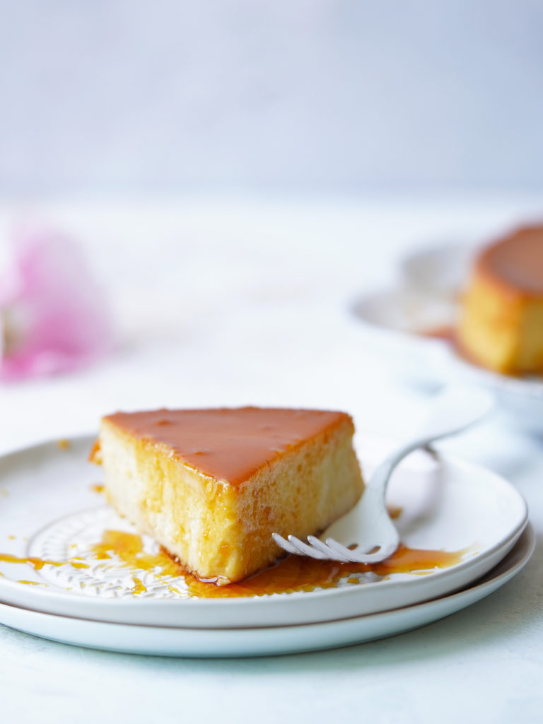 A slice of Mexican flan on a dessert plate and a white fork on the side.
