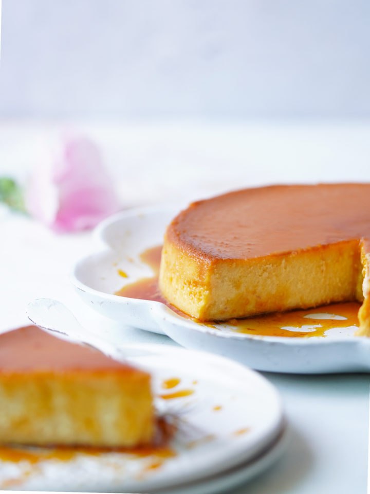 A slice of flan and the entire flan in the background.