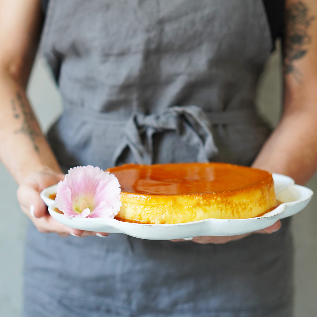A woman holding a platter with flan on top