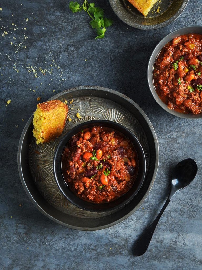 Two bowls of beef chili with a spoon on the side. Served with corn bread