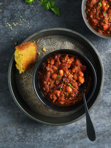Beef Chili in a black bowl with corn bread on the side