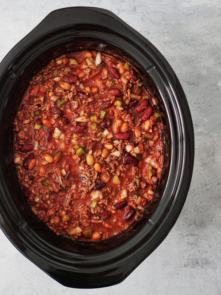 A crockpot bowl with ground beef, spices, beans, celery, bell peppers & onions. All mixed in.