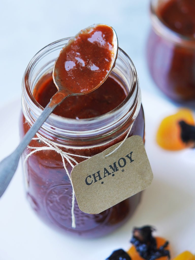 Chamoy on a spoon with a jar and a Chamoy sign