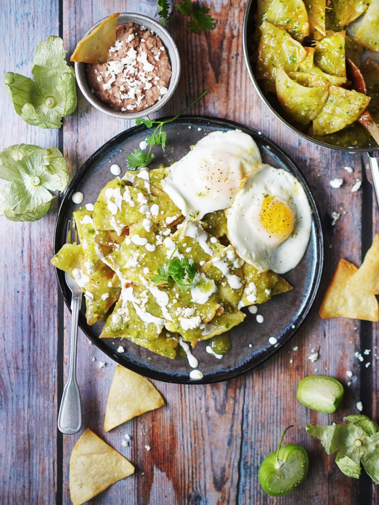 Wood table with chilaquiles on a dark plate