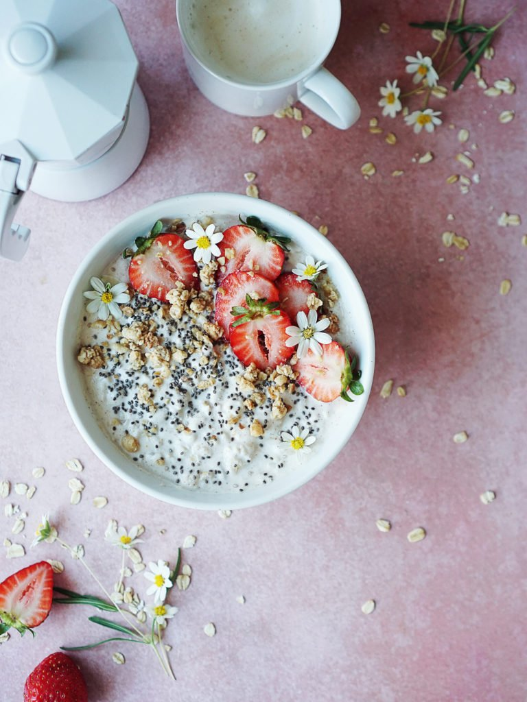 A bowl filled with yogurt and oats topped with strawberries