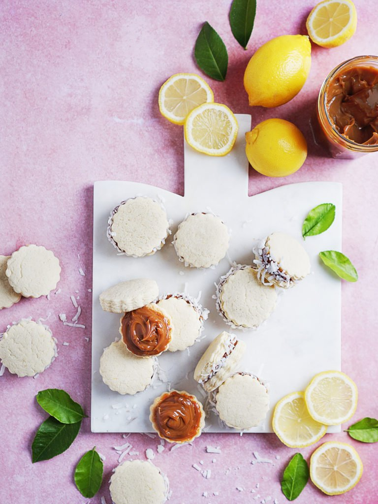 Alfajores on a small white board with fresh lemons on the side