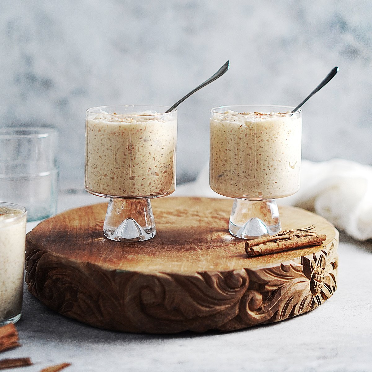 Two small glasses with arroz con leche and a spoon.