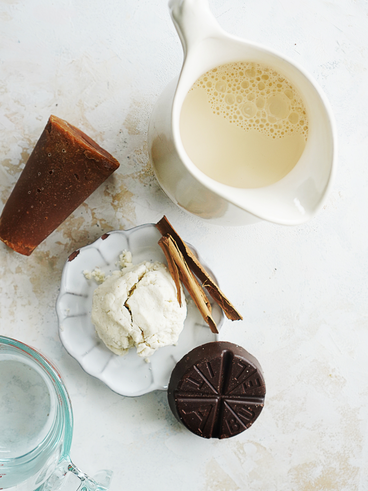 Ingredients: milk in a small jar, masa, piloncillo, chocolate in a circle and cinnamon stick