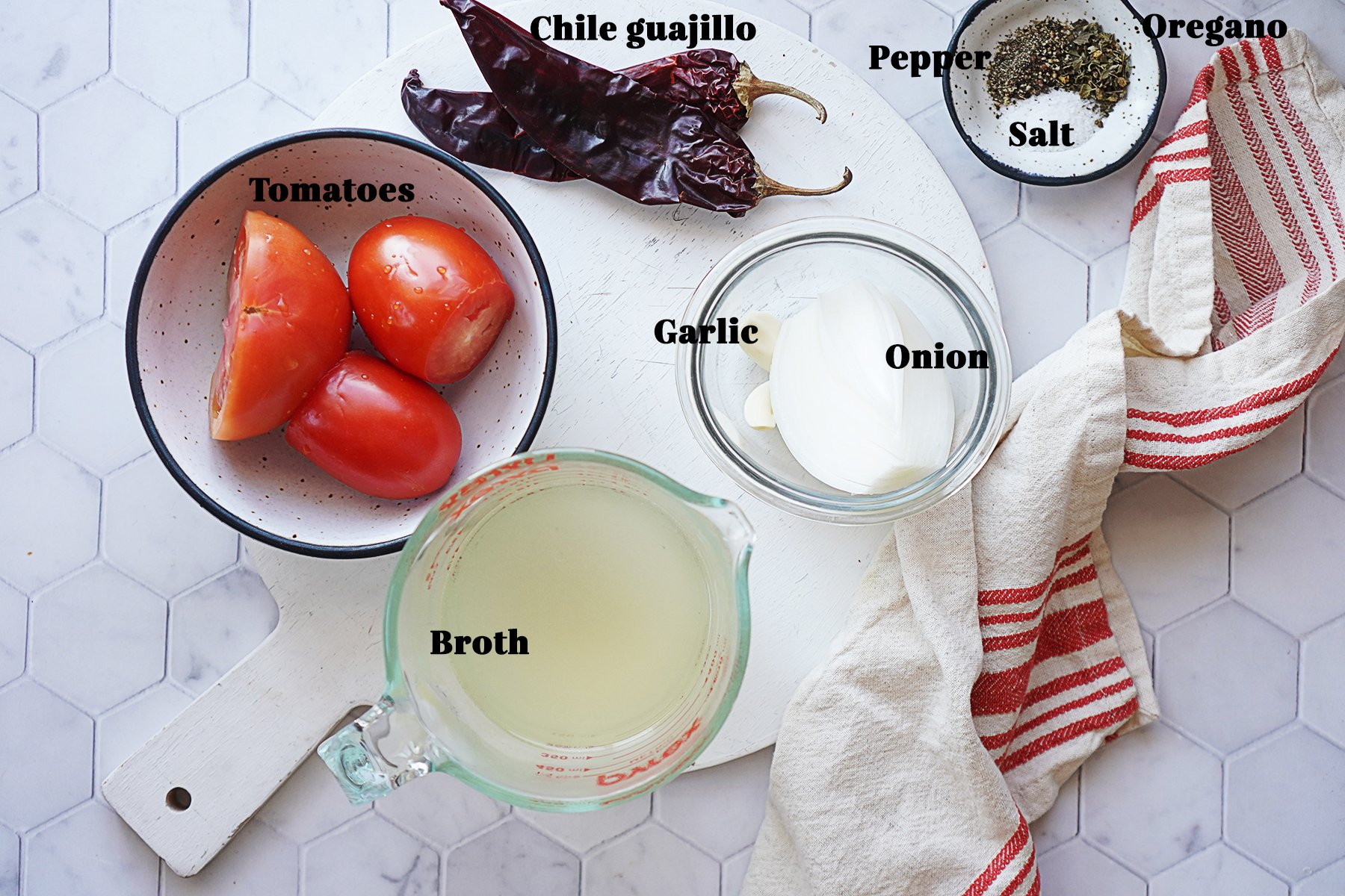 Ingredients on a white board: tomatoes, chile guajillo, garlic, onions, broth, and spices.