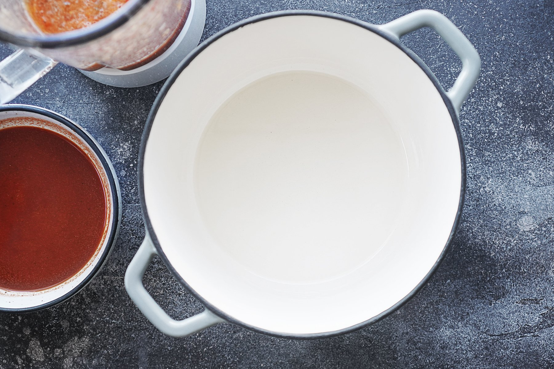 A white saucepan with sauces on the side to cook