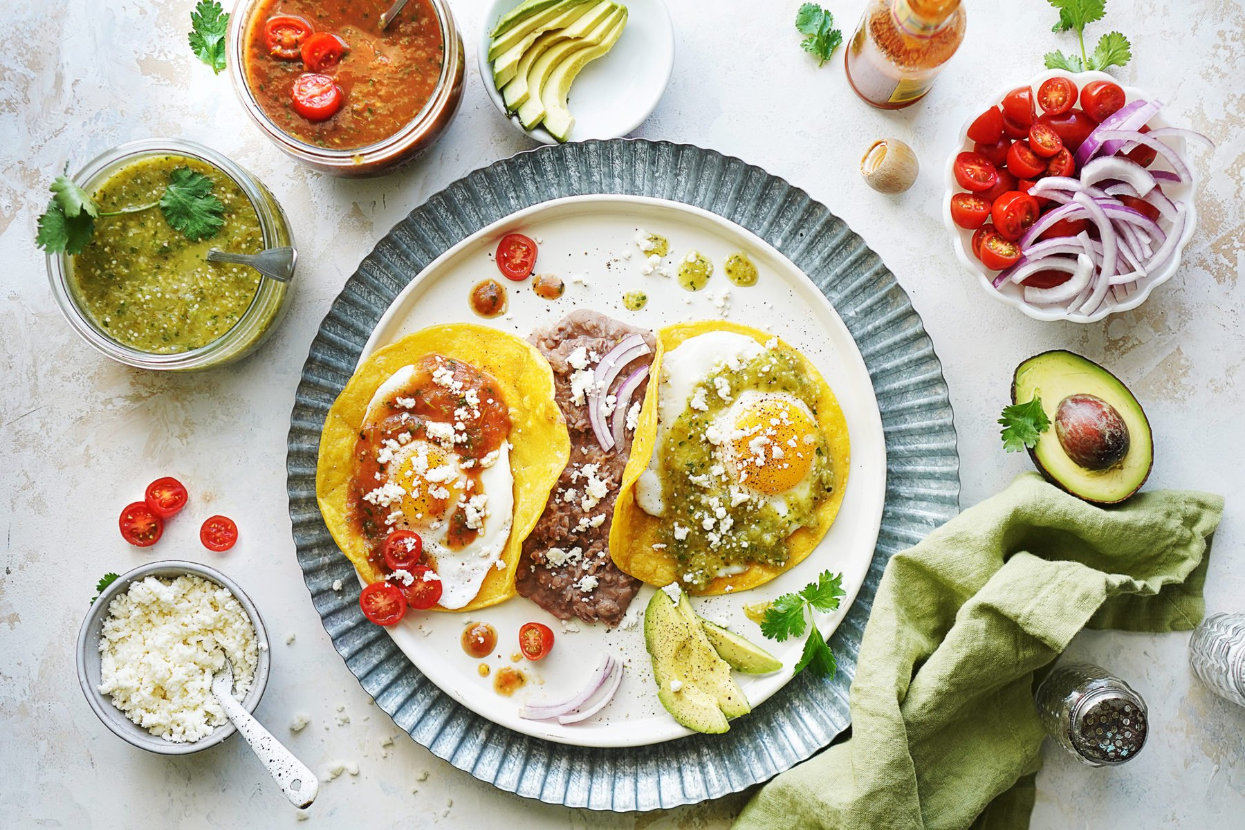 A table top with a plate with eggs, salsas on the side, avocado and queso fresco