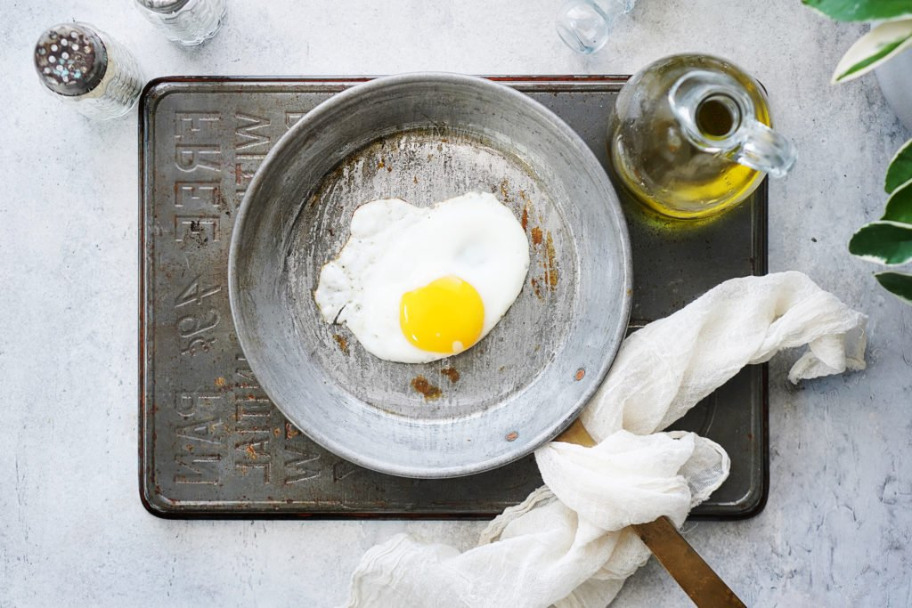 Frying one egg on a small skillet with a bottle of oil on the side