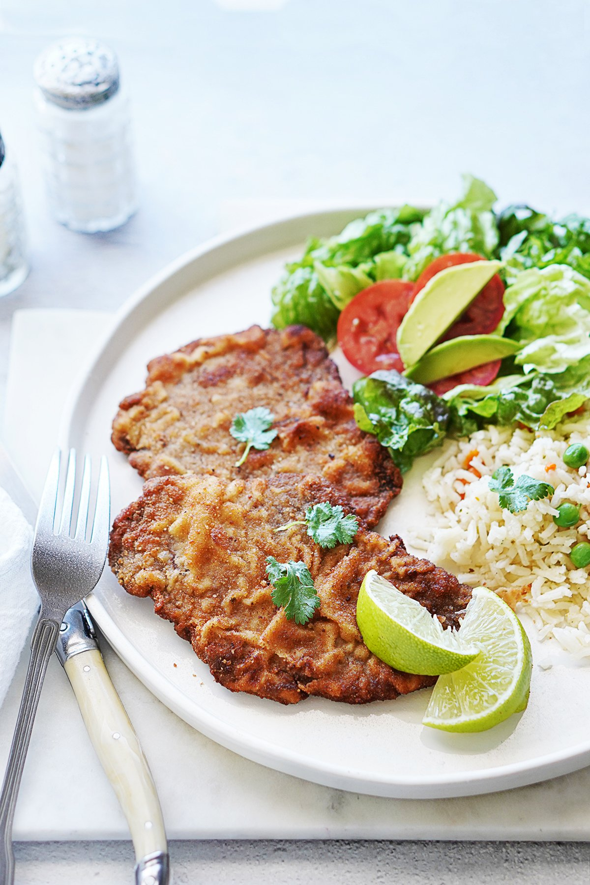 A plate with Milanesa, salad and white rice with a fork and knife on the side