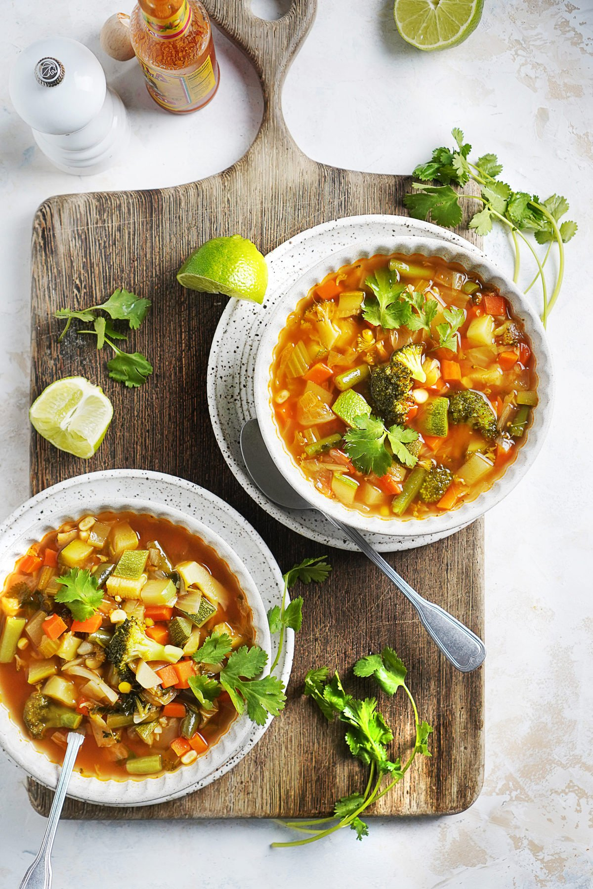 Two bowls with healthy Mexican soup on top of a wood board.