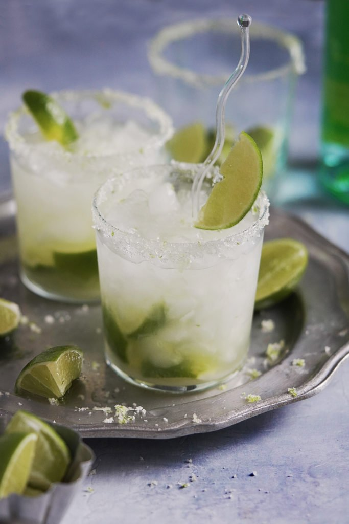 Caipirinha served with crushed ice and limes scattered around.