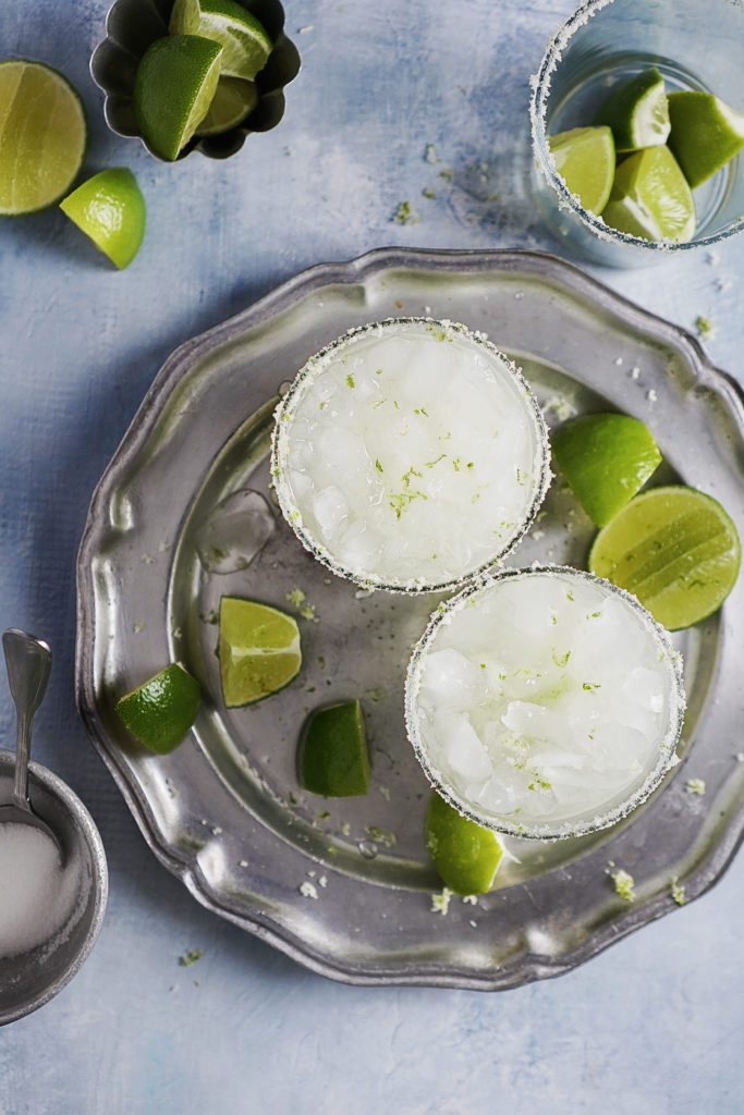 Two glasses filled with limes, sugar and crushed ice.