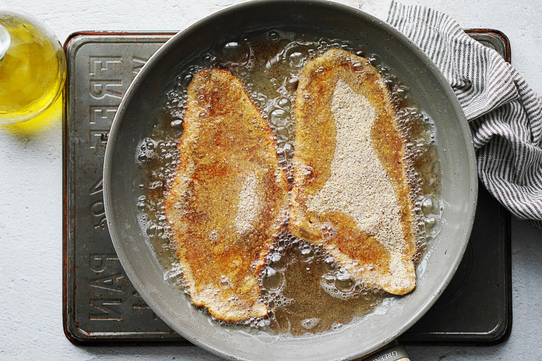 Frying breaded steaks in hot oil in a skillet