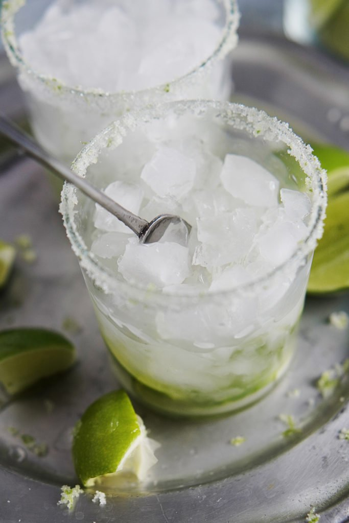 A glass with crushed ice and limes being mixed together
