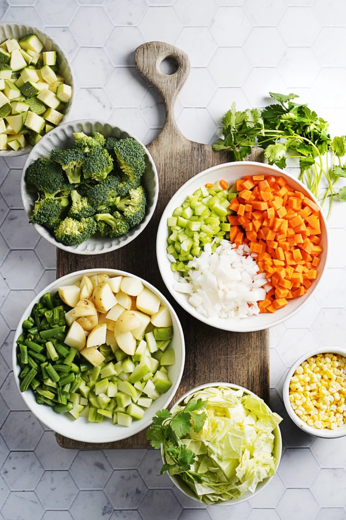 Cut vegetables placed on bowls on a cutting board