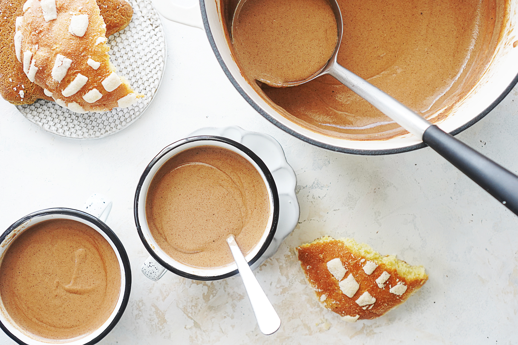 A saucepan with mexican chocolate drink and two mugs and sweet bread on the side