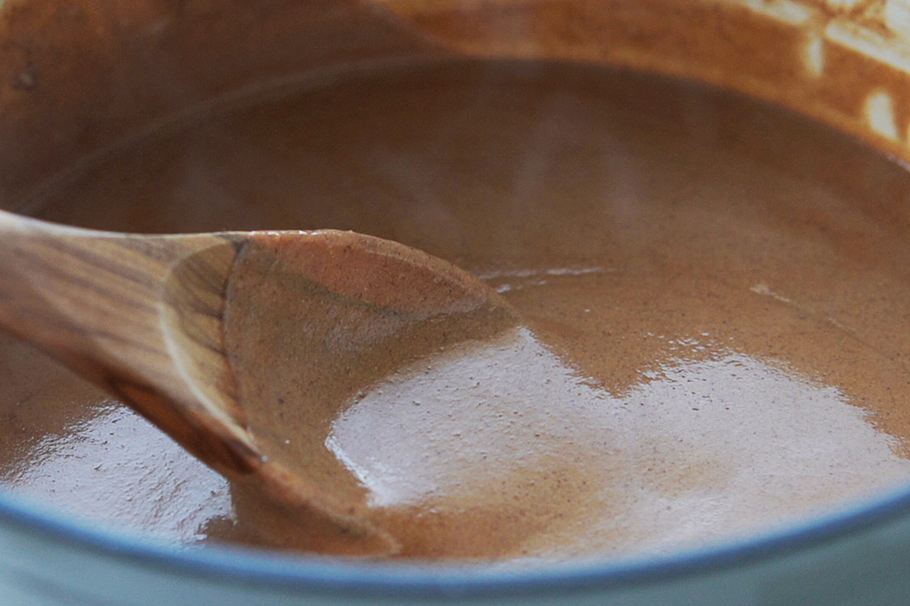 A saucepan with champurrado and a wood spoon.
