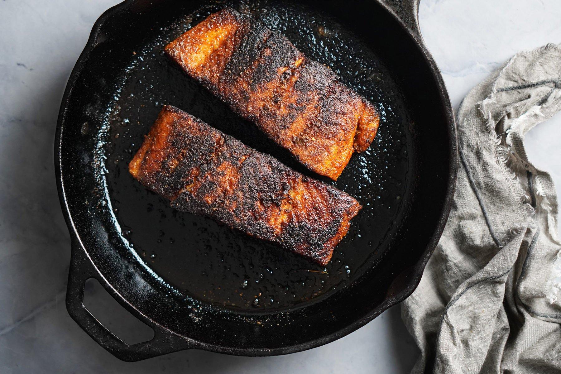 Blackened Salmon cooking on an iron skillet