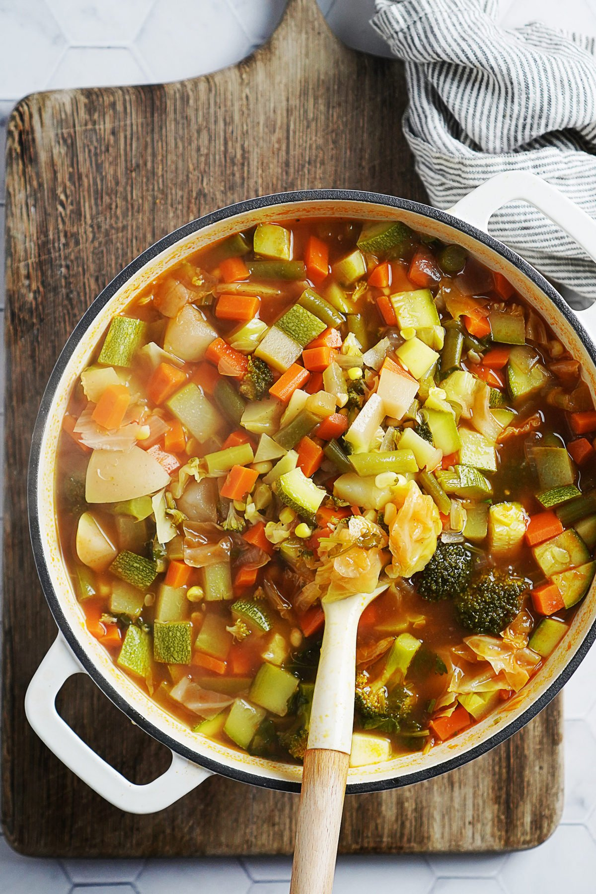 Stirring the vegetable soup with a white cooking spoon