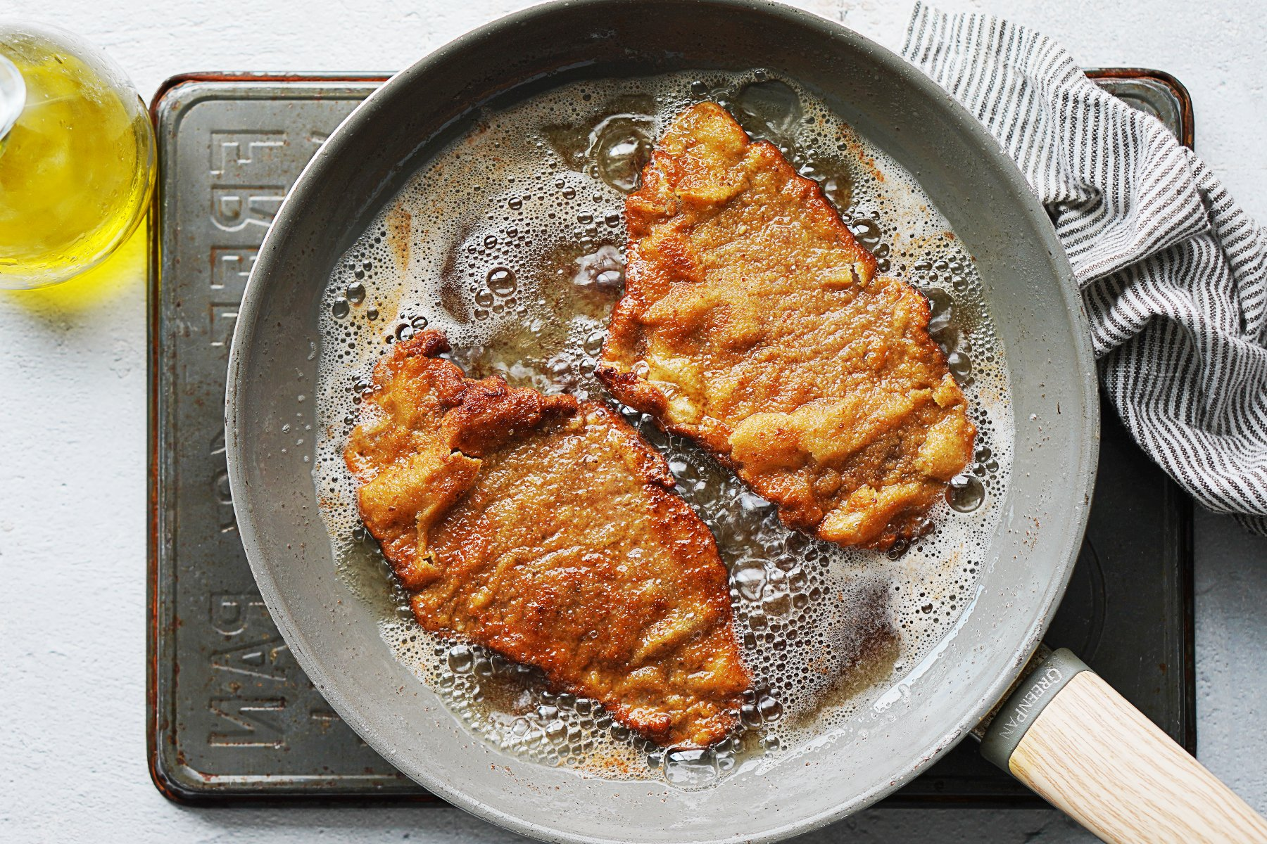 Cooking crispy breaded steaks in a skillet