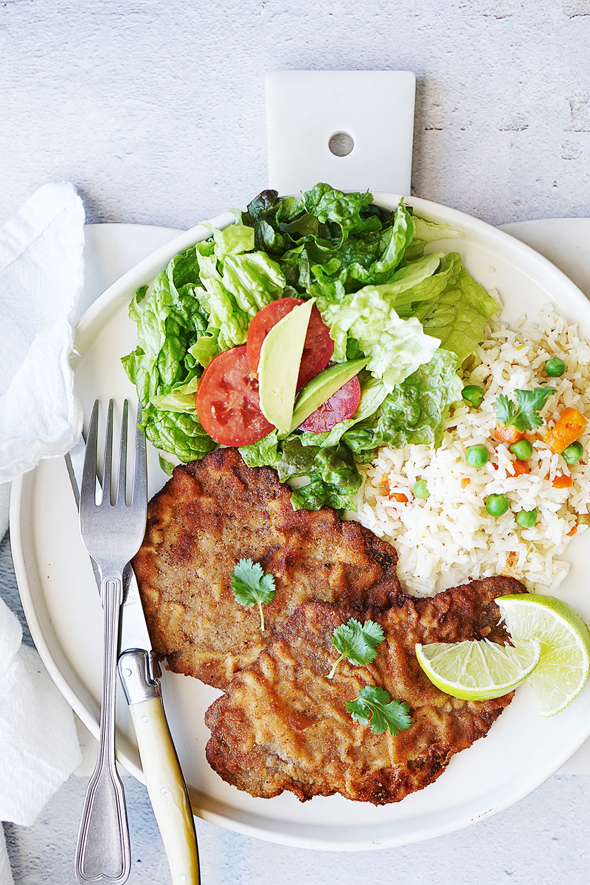 A plate with breaded steaks, salad and white rice with a fork and knife on the side