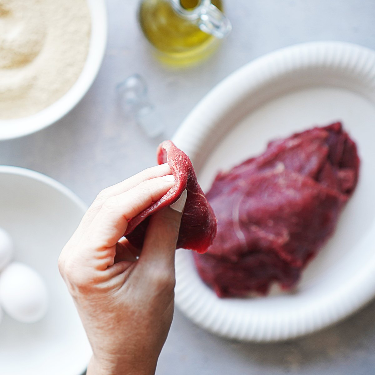 Think steak cut held by a hand.