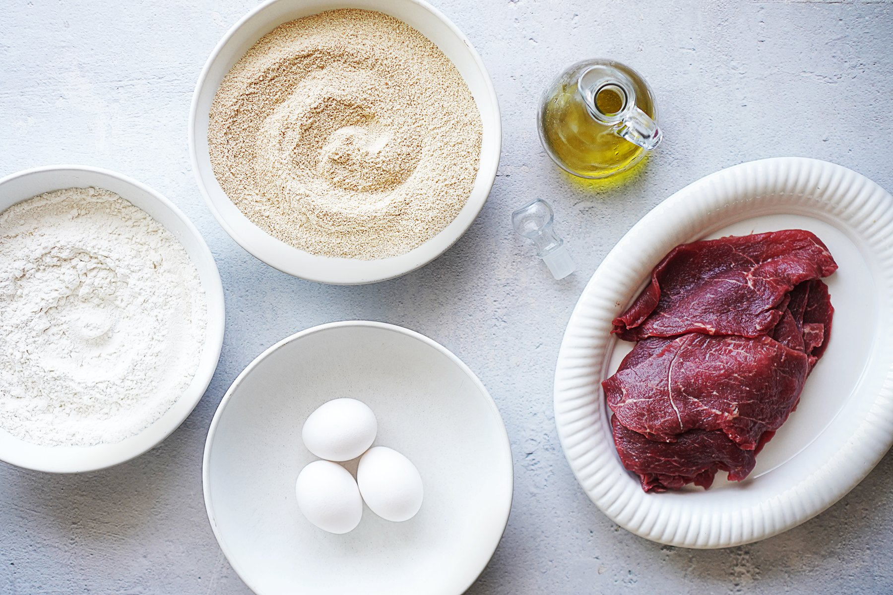 Ingredients in separate bowls: flour, breadcrumbs, three eggs, oil and thin steaks