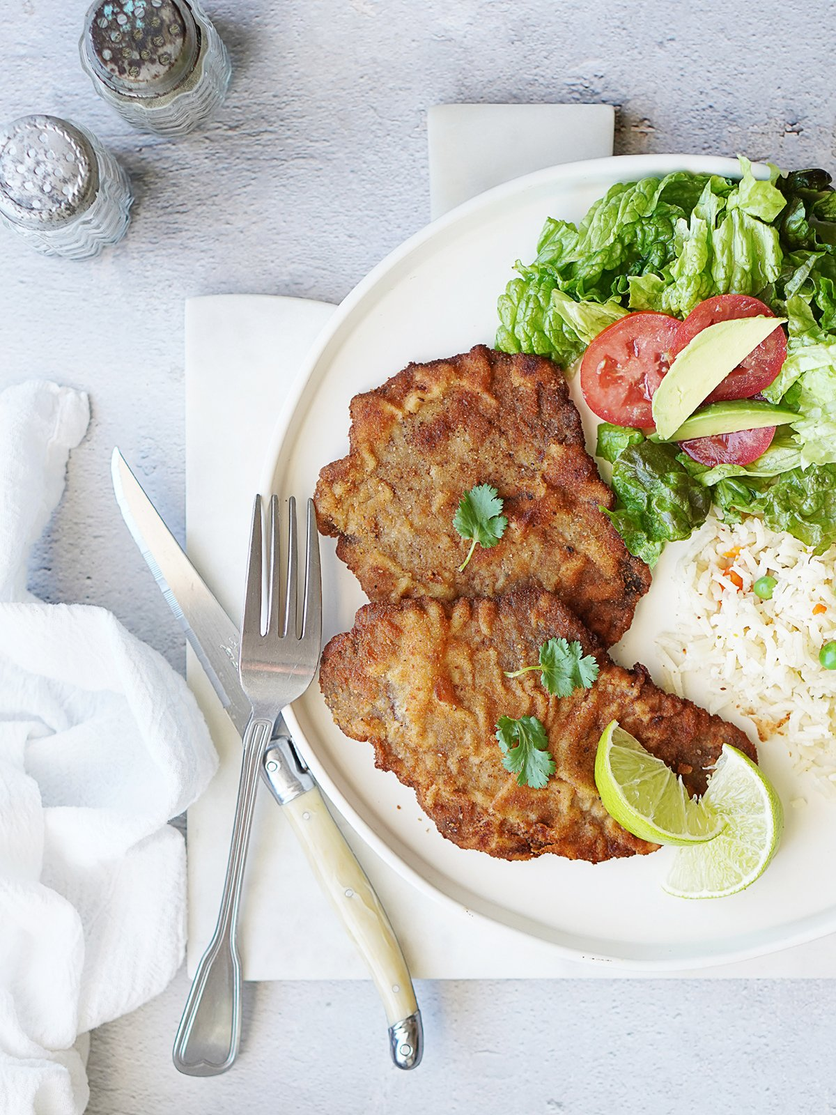 Two milanesa steaks on a plate with rice and salad