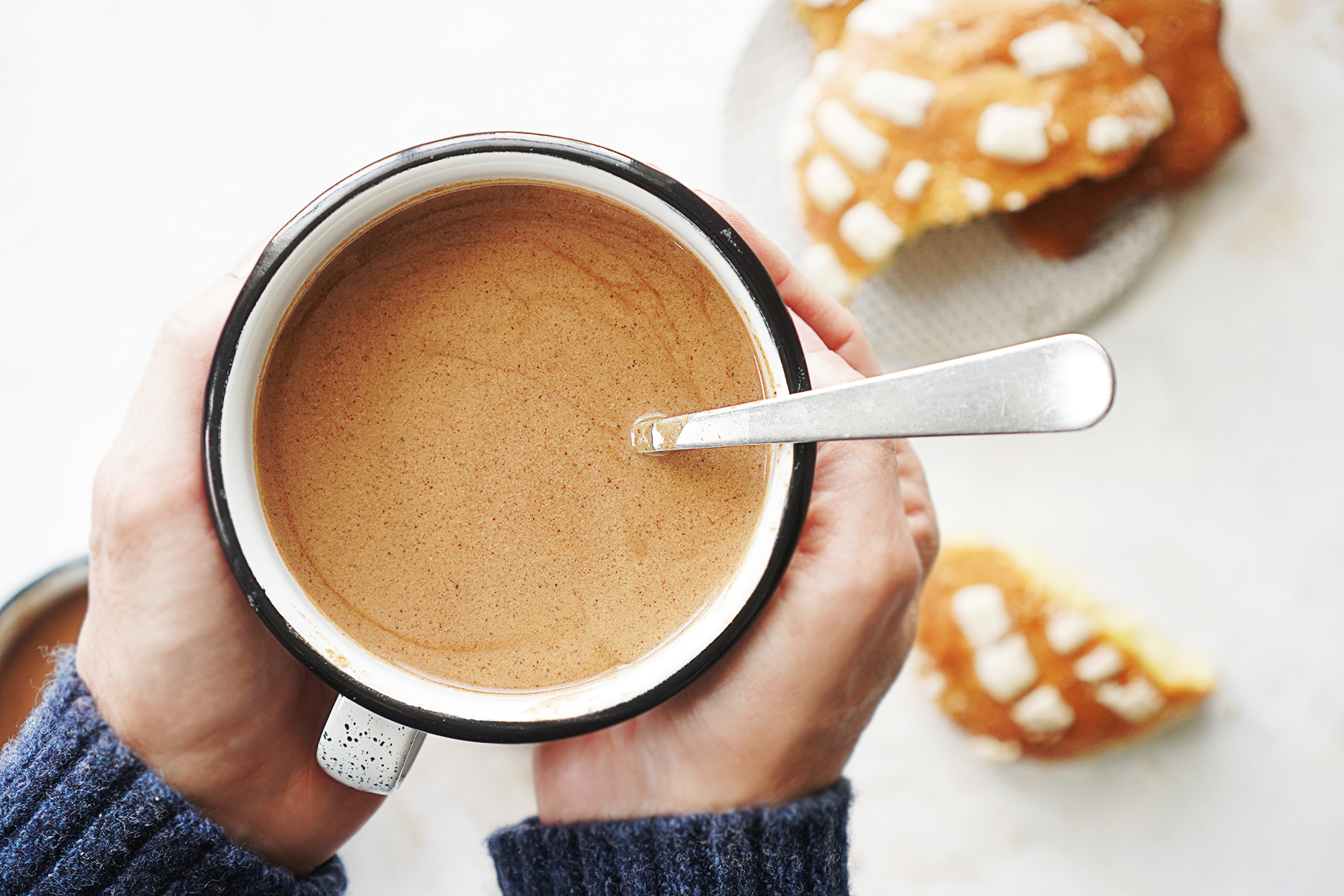 Two hands holding a mug with Mexican chocolate and spoon in the cup