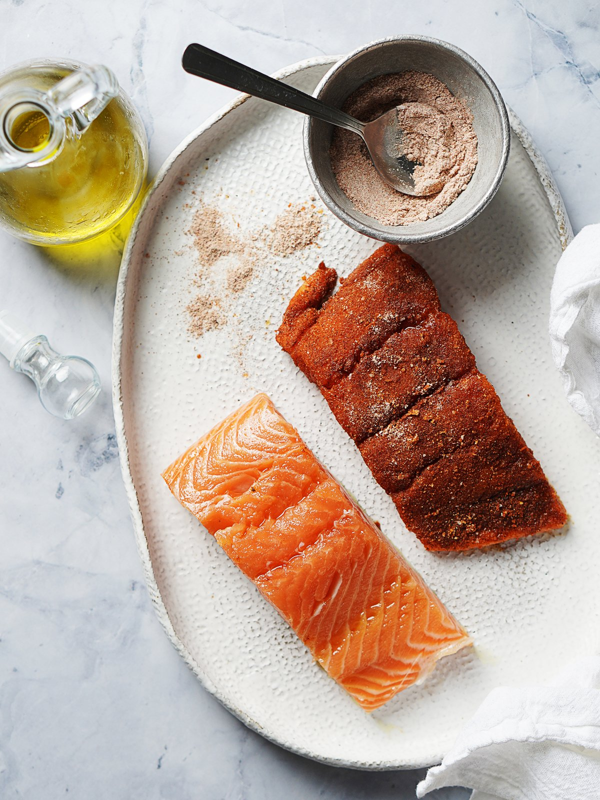 Two pieces of salmon: one with the spice rub and one without.
