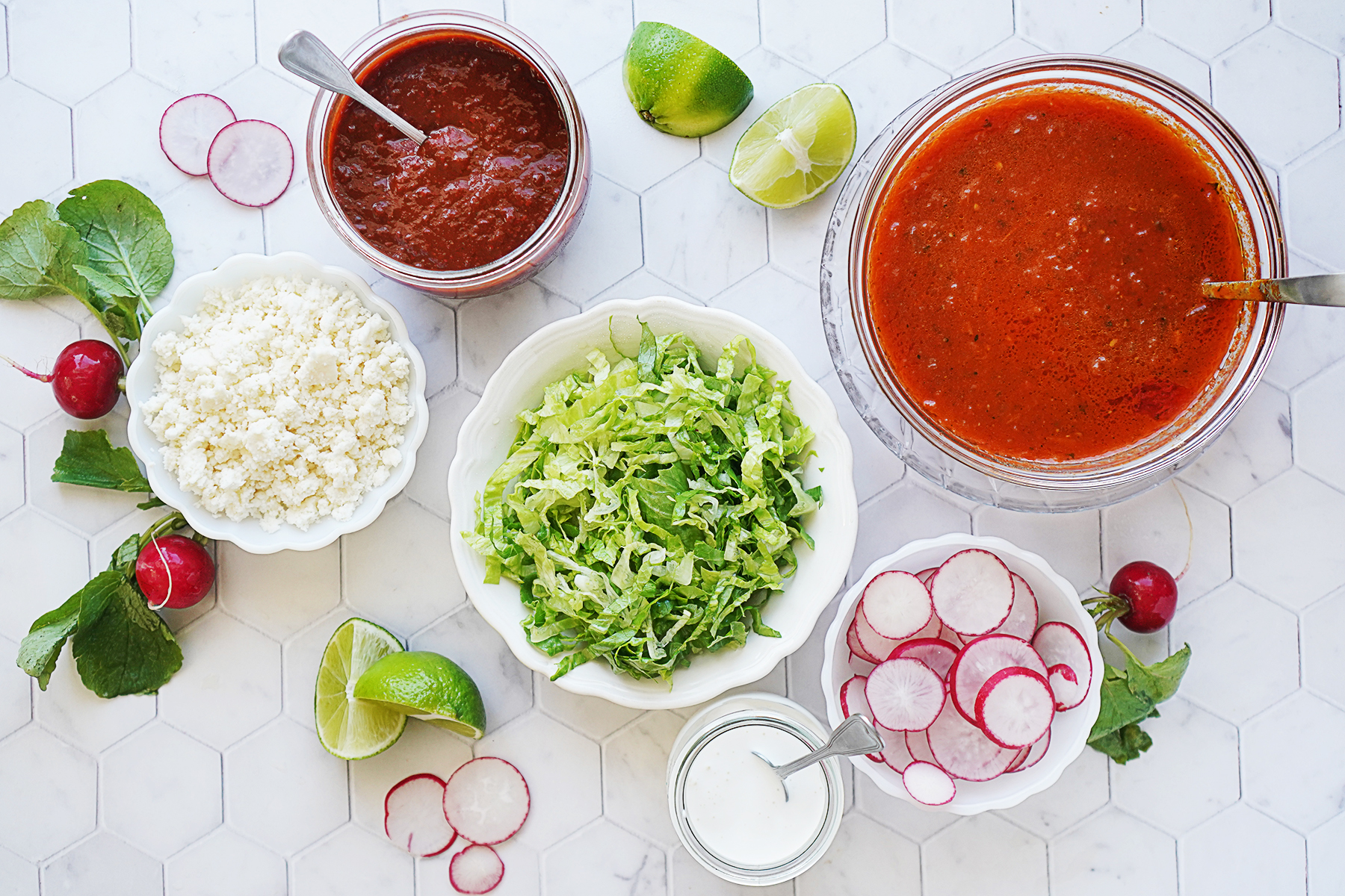 Toppings in small bowls: crumbled queso fresco, salsa, consome, shredded lettuce, sliced radishes & crema