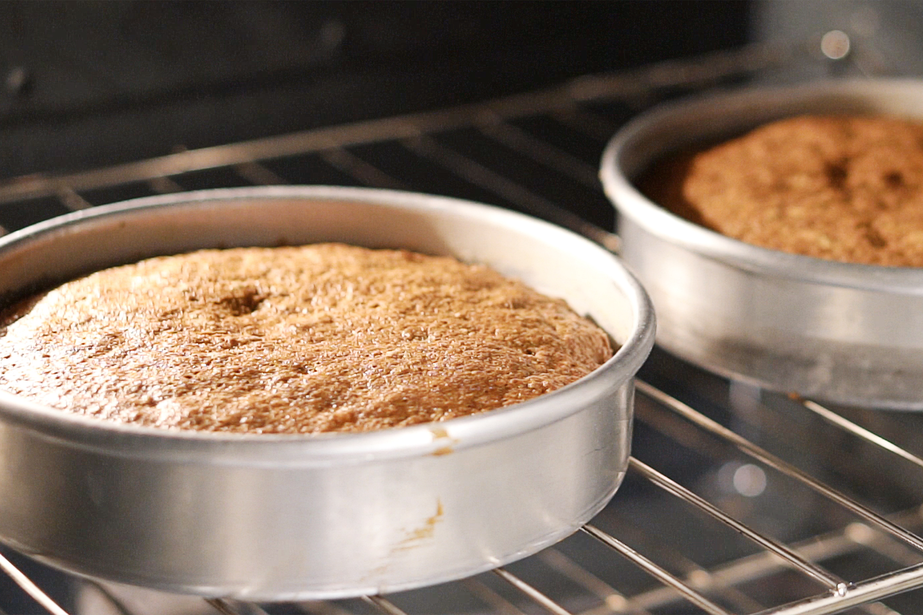 Two cakes baking in the oven